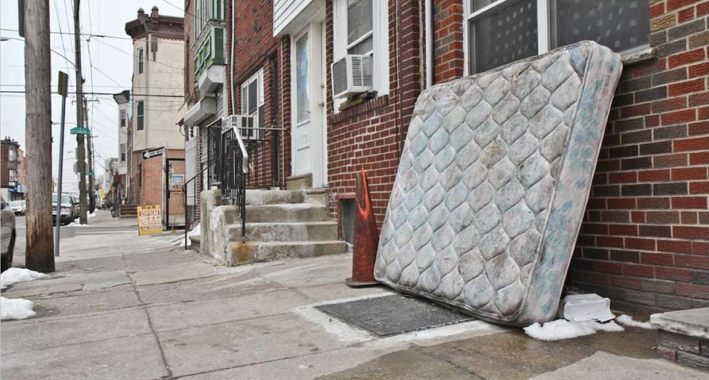 Mattress sitting on the side of the building waiting to be thrown away