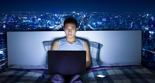 A man using his laptop before bed time