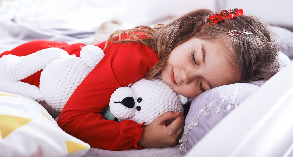 child sleeping peacefully in bed