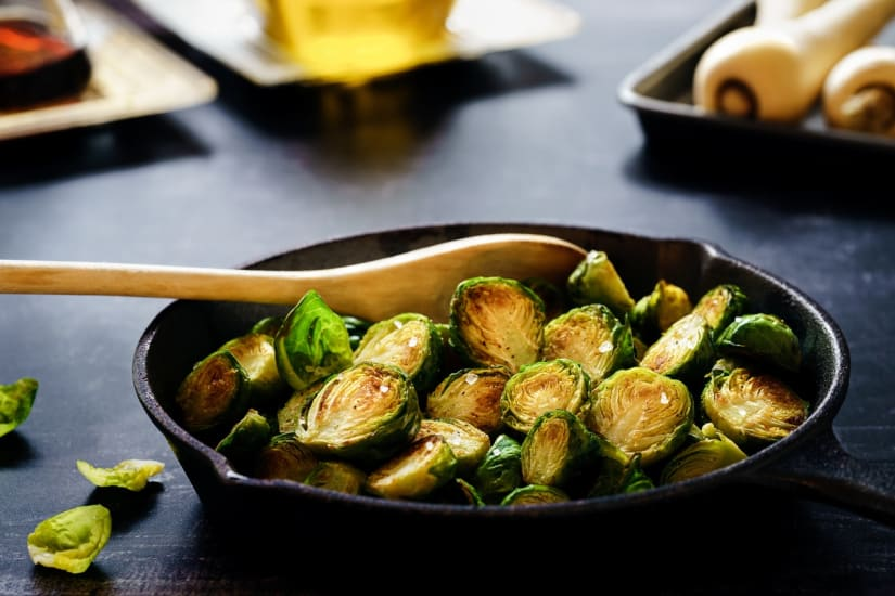 Brussel sprouts in a pan next to wine for vegetarian food
