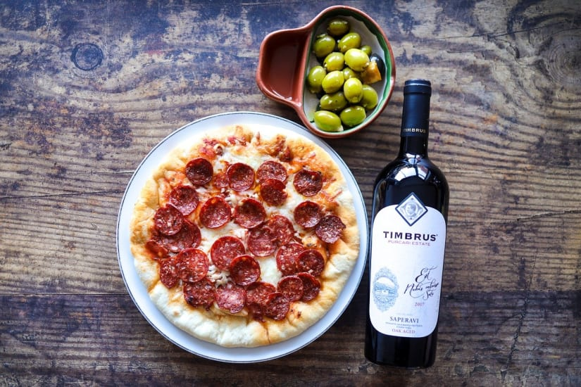 Best wine for pizza next to a pepperoni pizza and olives