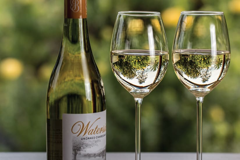 unoaked chardonnay bottle next to two filled glasses