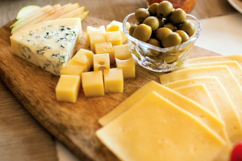 ostbricka med gröna oliver