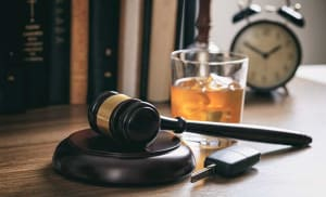 Gavel, drink and a car key on a attorney's desk