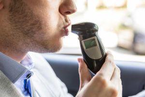 Guy taking a breath test inside his car