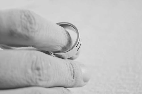 a person holding a wedding ring