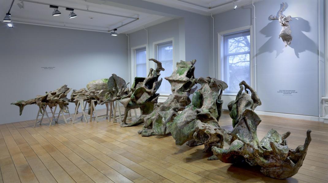 """Maartje Korstanje, """"Metamorfose"""", solo expositie Museum Jan Cunen.  Lucette ter Borg: uit Essay in de publicatie 'Metamorfoses' Maartje Korstanje, Museum Jan Cunen:Maartje Korstanje past in een traditie van eenentwintigste-eeuwse beeldend kunstenaars die de dogma's van het modernisme ver achter zich hebben gelaten. In 1970 stelt de Nederlandse kunsthistoricus Carel Blotkamp de regels nog dapper op scherp. 'Het beeld is autonoom en in zichzelf besloten', schrijft Blotkamp.' Dat wil zeggen dat (het kunstwerk) niet verwijst naar onderdelen van de zichtbare werkelijkheid'.Hoe langer je naar het beeld kijkt, hoe sterker de indruk ontstaat dat wat je hier ziet ook weer tot leven kan komen, een ziel kan krijgen, een 'ik' kan worden die spreekt tot de toeschouwer. Dat 'ik' onttrekt zich gek genoeg juist aan menselijke aanwezigheid. Dat 'ik' ademt, rust, observeert al zo lang als mensen zich dat kunnen heugen en nog langer. Dat 'ik' – ik geef het toe- is een subjectieve interpretatie, een associatie die misschien ik alleen heb. Korstanje's beelden lokken die interpretaties en associatieve verbanden uit. Ze zijn, zoals arte povera-kunstenaar Jannis Kounellis eens mooi omschreef: 'de terugkeer van de poëzie op alle mogelijke manieren'. Maar ze zijn meer. Ze zijn van morgen, van nu en van gisteren. Ze liggen, hangen en staan verdroomd te wezen in een tijd die alleen hen toebehoort. Soms denk ik weleens dat ze de tijd zijn- dat vreemde fenomeen waarvan je je wel een voorstelling kunt maken, maar niet exact kunt aanduiden wat het is. Foto GJ v Rooij. Collectie Museum Jan Cunen."""