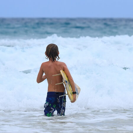 Boy standing with surfboard looking at ocean