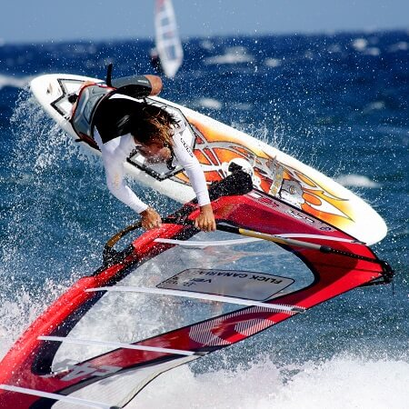 A wind surfer jumping off of a wave