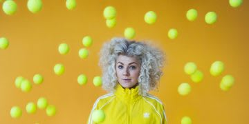 Blogger Leni is standing in front of a yellow background wearing a yellow adidas tracksuit while tennis balls are flying through the air. Adidas; GamePlan A; Color; Creativity; Inspiration; Blogger; adicolor; Colorful; Blog
