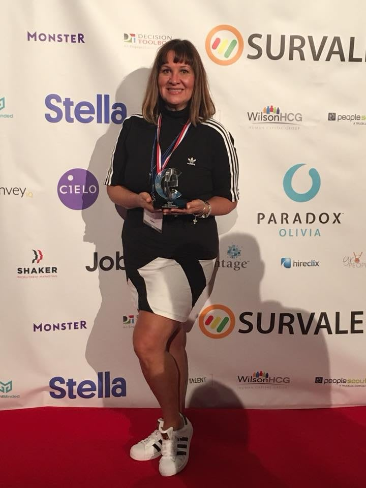A woman receives an HR award for quality recruitment on a red carpet