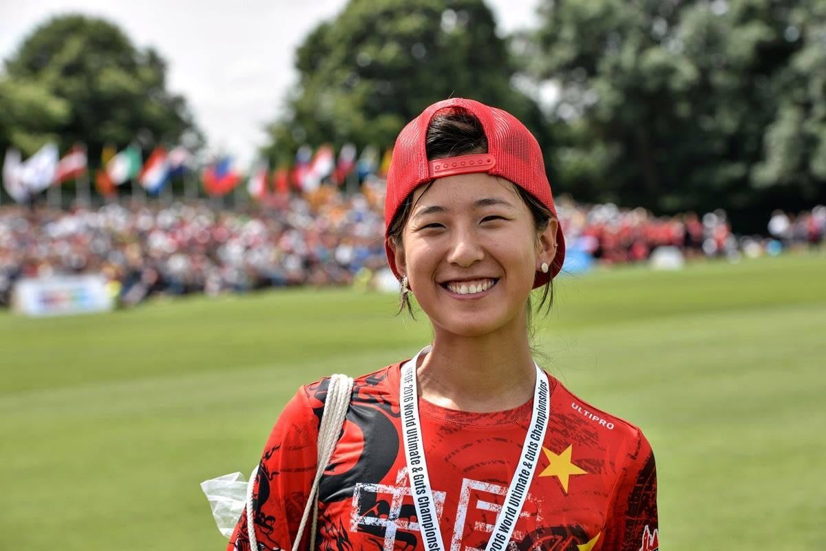 A Chinese female frisbee player smiles at the camera with your fed hat flipped back and her medal around her neck.