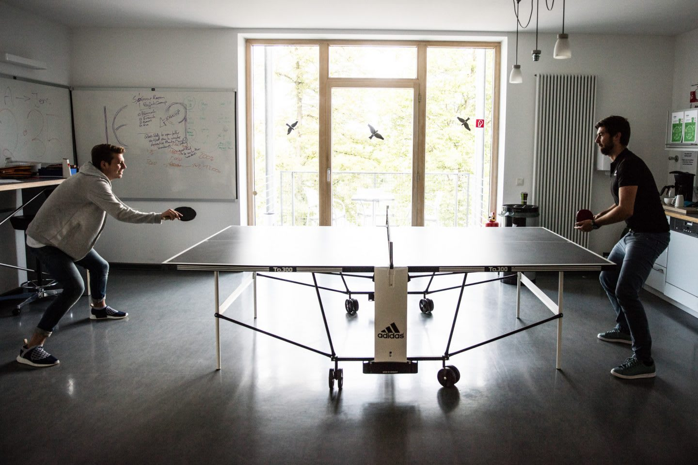Two colleagues play a round of table tennis inside before starting their work day.