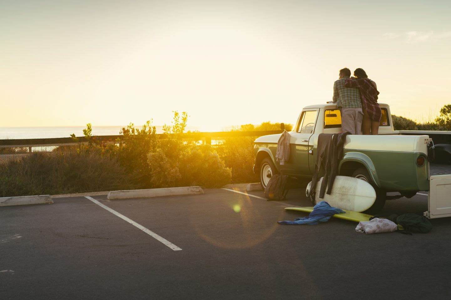 A van in the sunset with a couple on the deck relaxing on top of it_beach_chilling moments_happy days