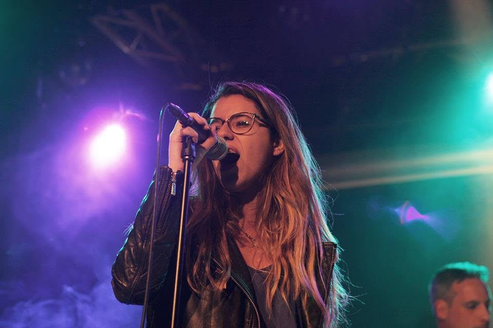 Lina Benabdesslem stands on stage signing. concert, singing, passion, singer, spotlight, stage.