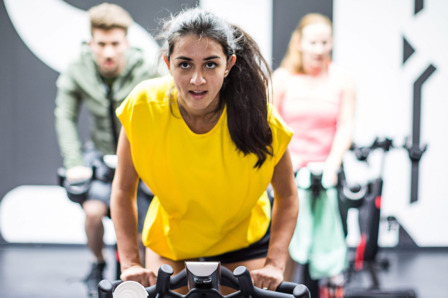 A girl wearing a vibrant yellow tshirt is motivated in an indoor cycling class. goal-setting, success, GamePlan A, confidence