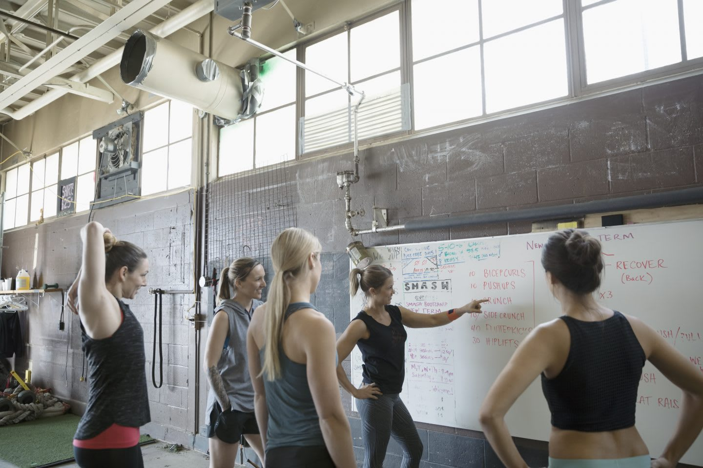 A female CrossFit instructor stands in front of a white board planning a class with her female students in a gritty gym. goal-setting, success, GamePlan A, confidence