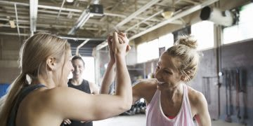 Strong and enthusiastic women high-fiving in gym. goal-setting, success, GamePlan A, confidence