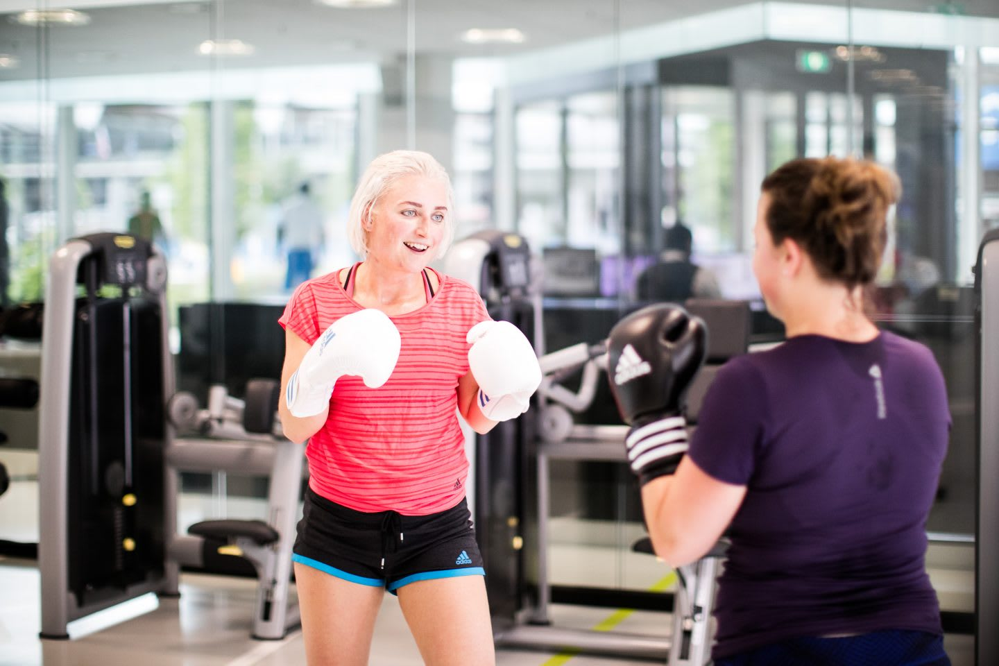 A female adidas employee enjoys boxing in a gym with a colleague. Boxing, Motivation, Confidence.