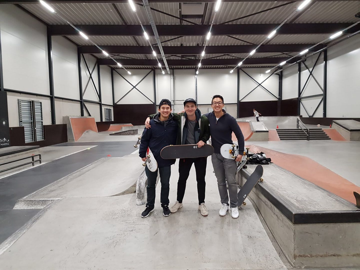 Three young men standing together linking arms after a successful indoor skating session. Skaters, Skateboarding, Friendship.