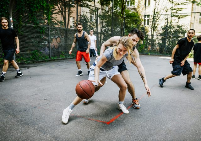 An amateur female athlete skillfully defends her position during a friendly outdoor basketball game in the city against her male competition. basketball, sports, gender, equality, passion.