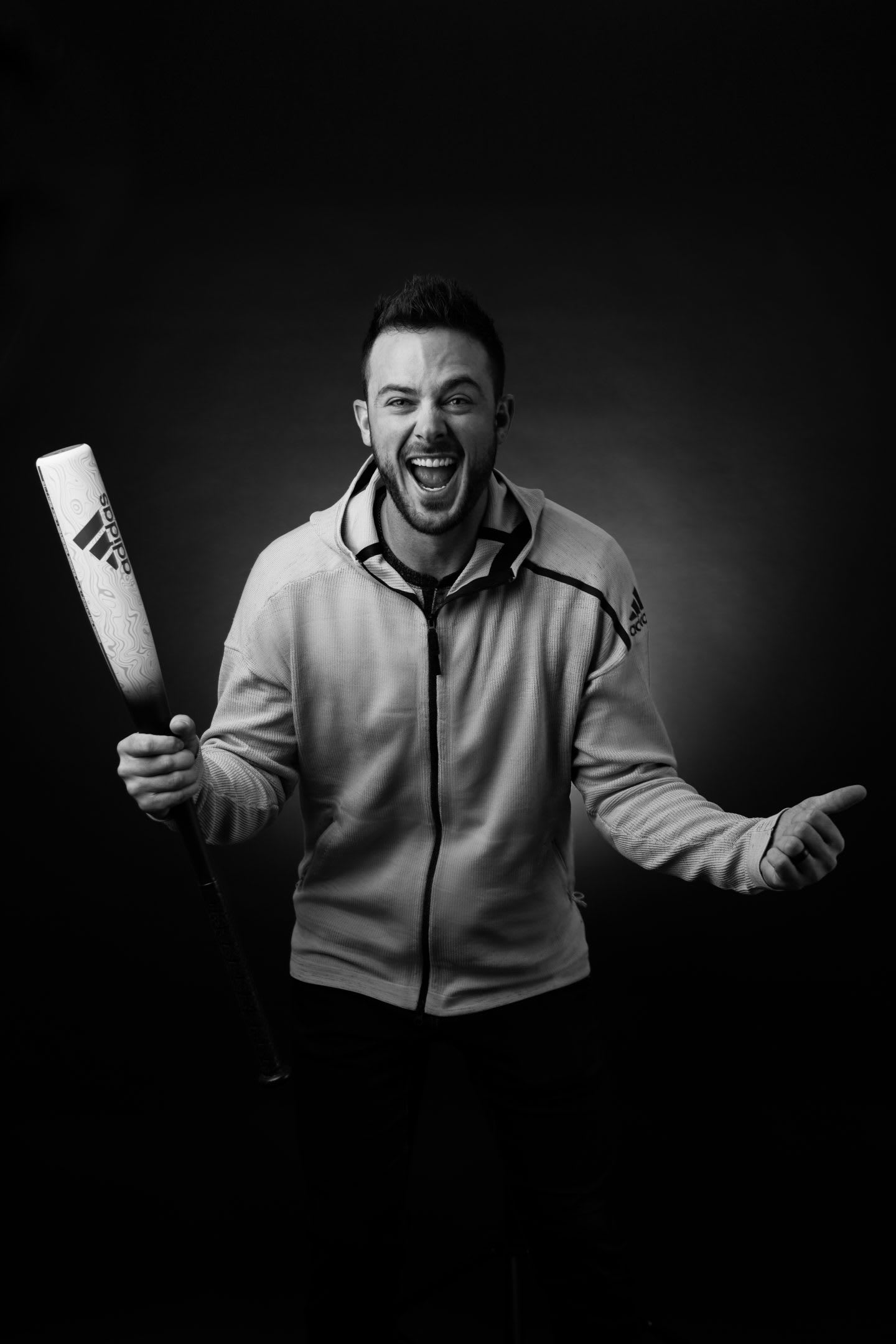 A baseball player grips his baseball bat in the air and roars with a smile. Athlete, baseball, baseball star, motivation, passion.