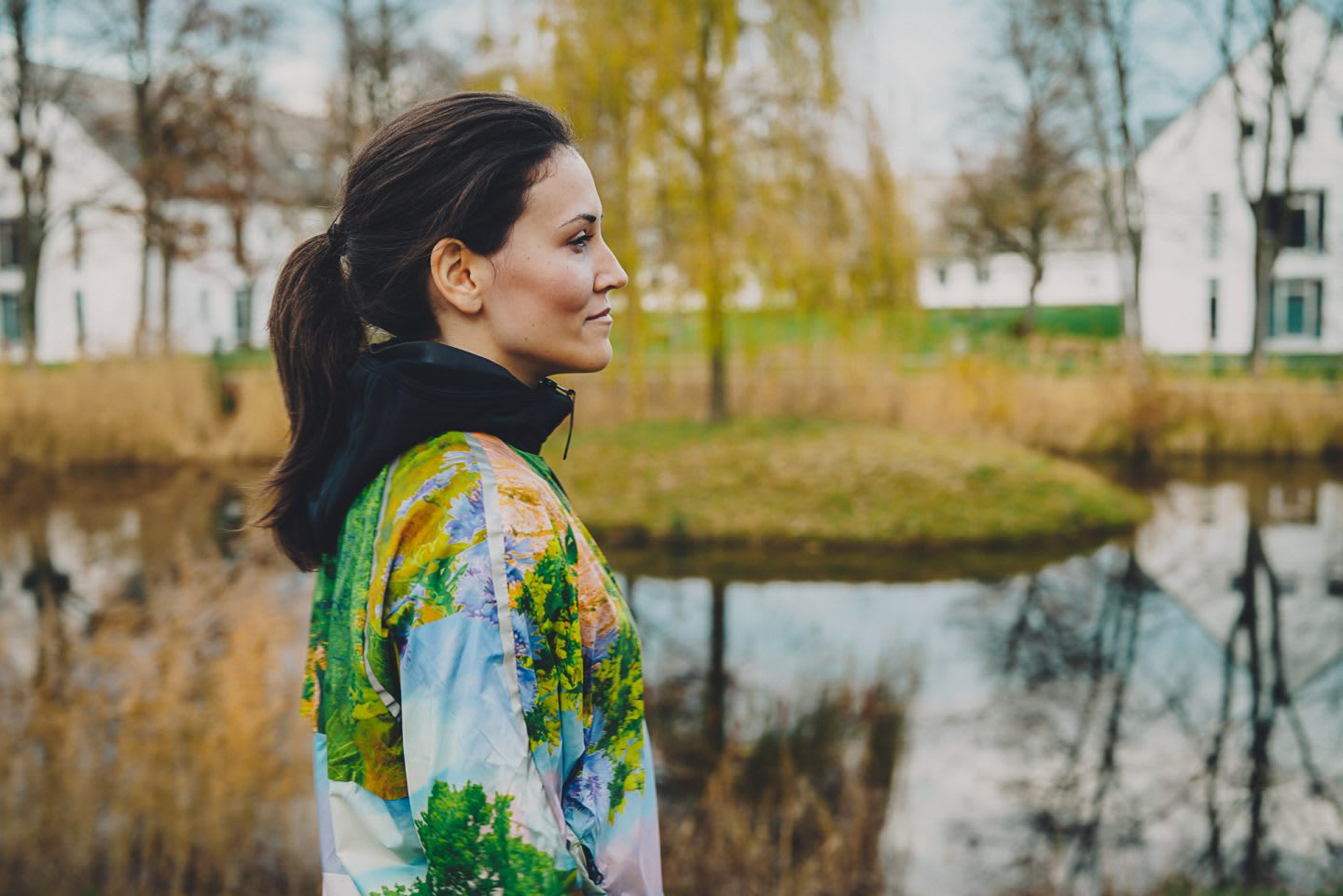 A woman wearing fitness clothing stands by a pond on a cold day. outdoors, environment, calming, peaceful.