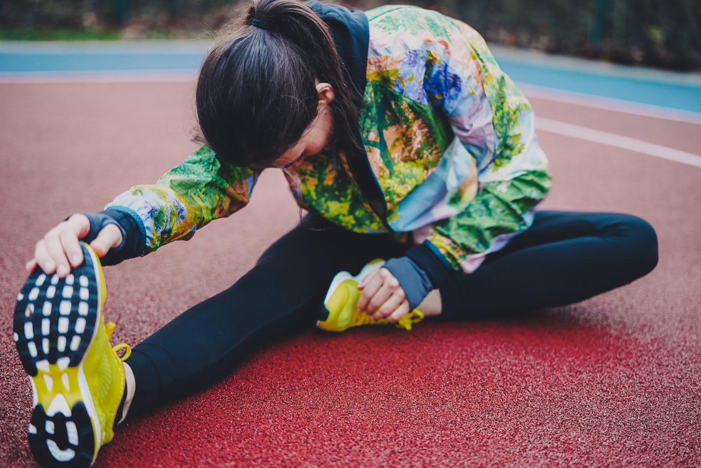 A woman stretches her right leg forward on the ground in preparation for a workout. stretching, preparation, process, routine.