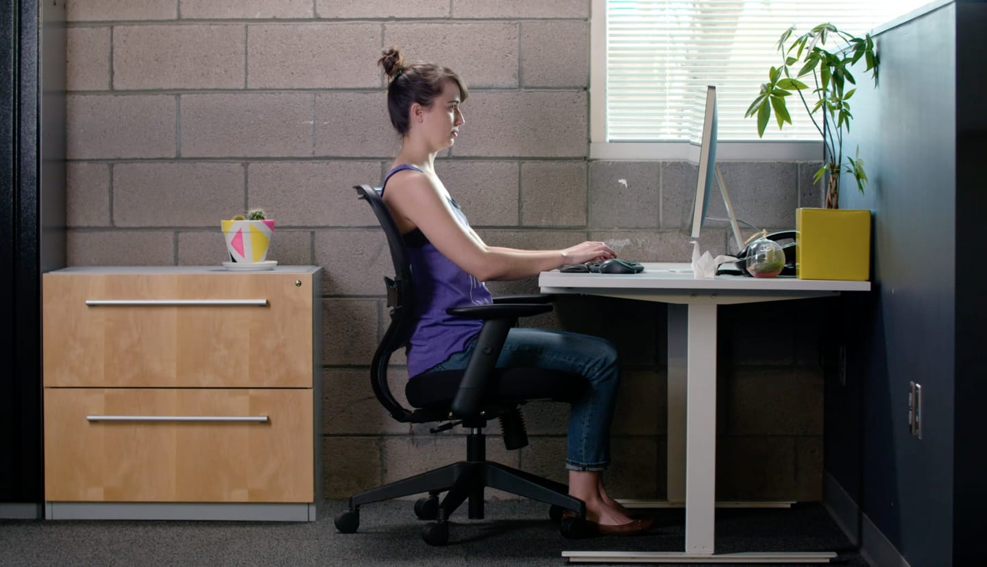 a woman sits at a desk typing on her computer. work, office, focus.
