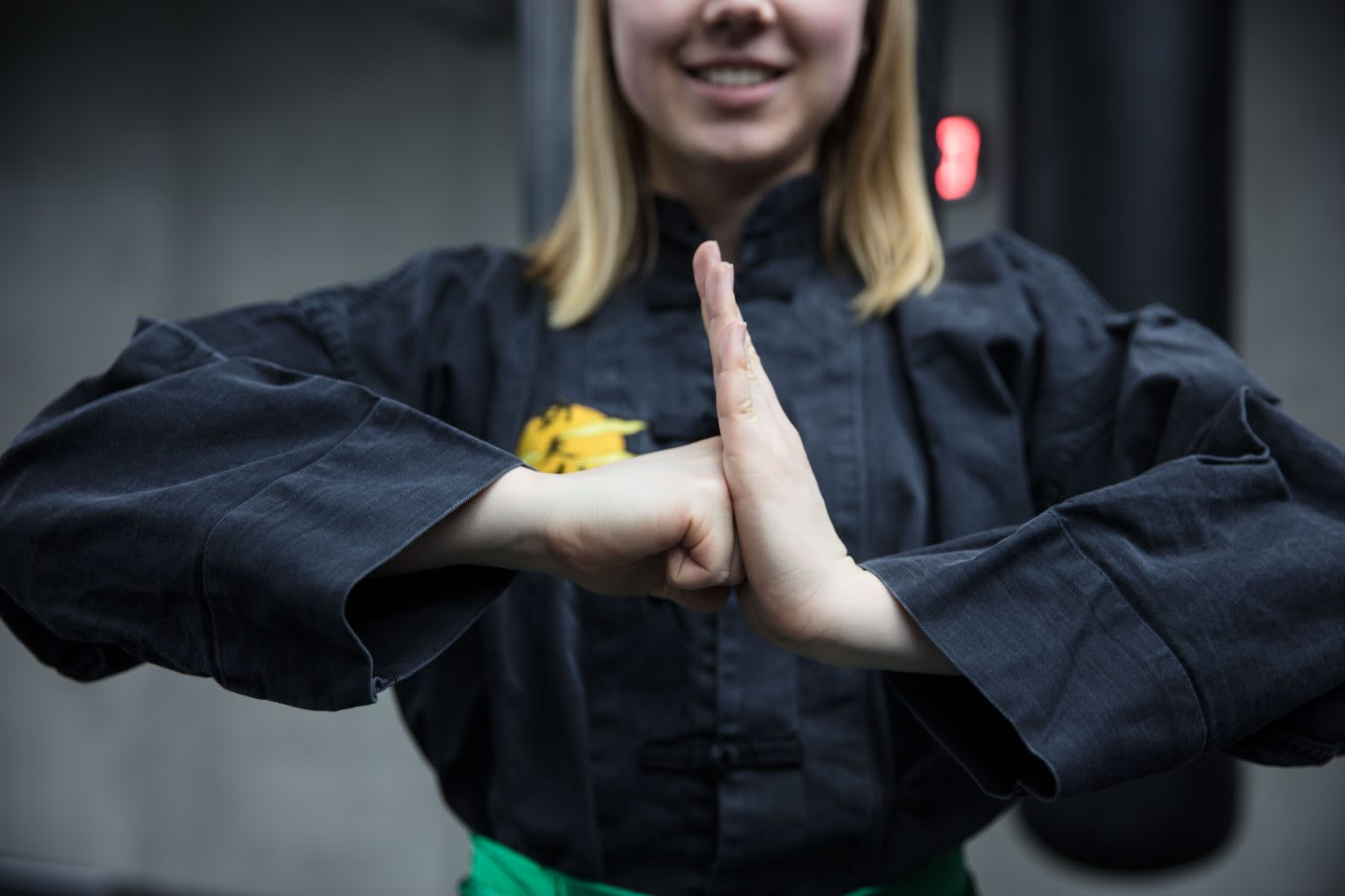 A woman wearing a black traditional kung fu uniform places her hands together in a thankful gesture. kung fu, respect, tradition, thanks