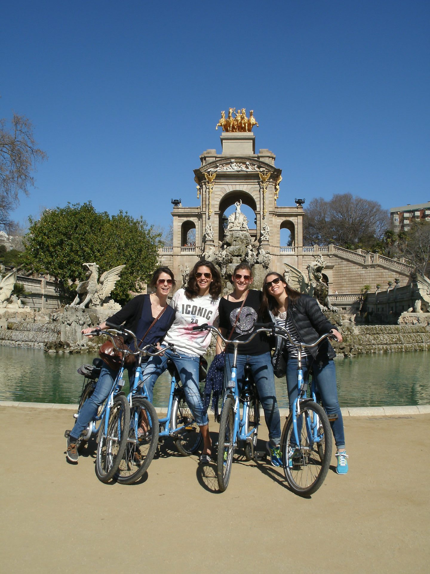 A group of friends sit together on the bicycles in front of a fountain in a park. friendship, bonding, guided tour, outdoors