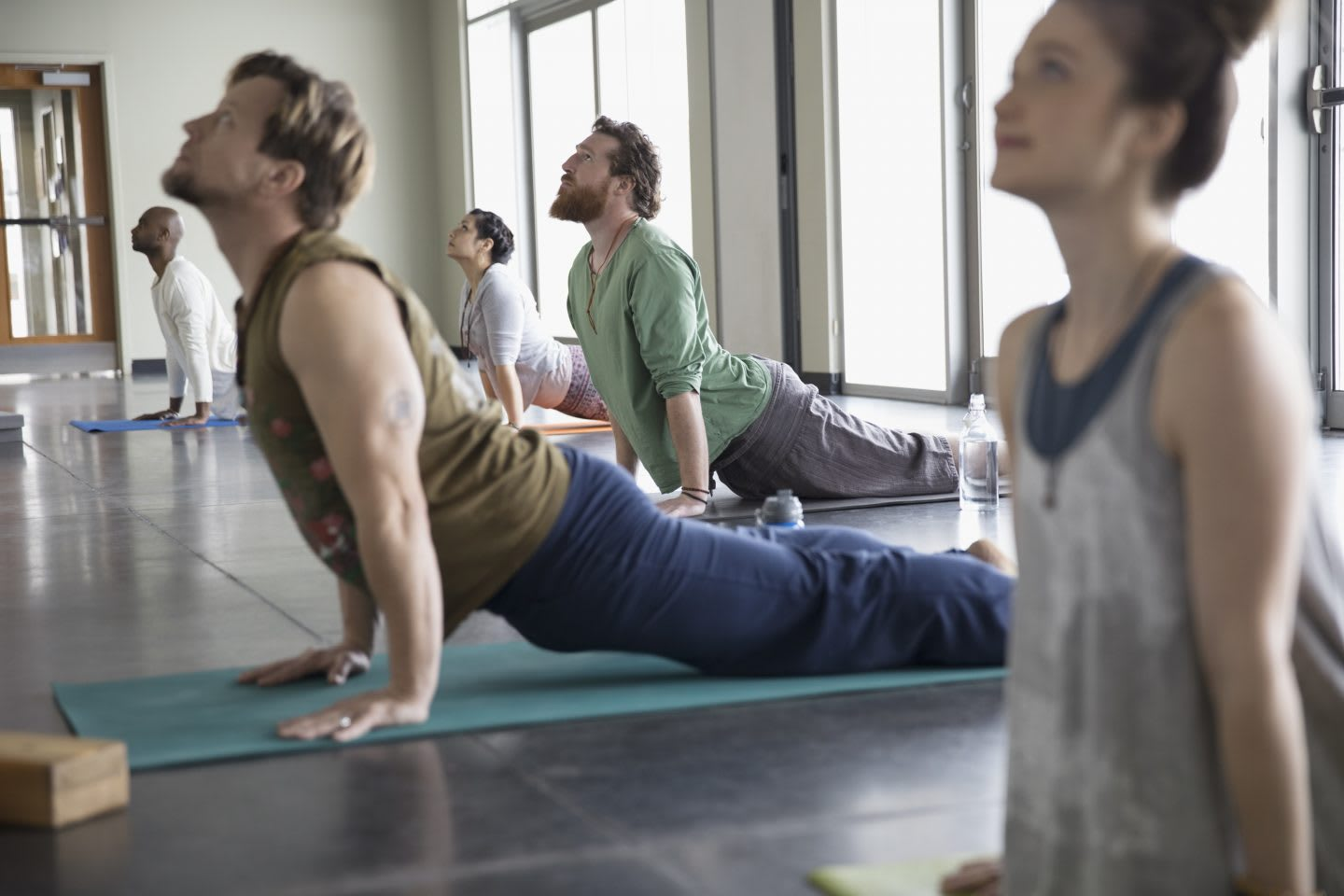 Men and women practicing yoga upward facing dog pose in yoga class studio. yoga, mindfulness, relax, activity