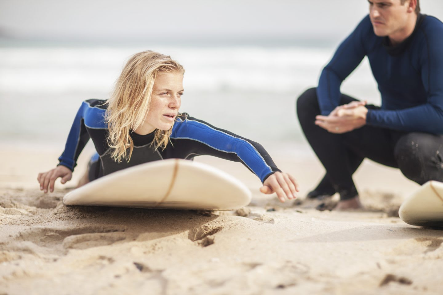 Man instructing woman on surfboard on the beach. learning, surf, student, beach, sand