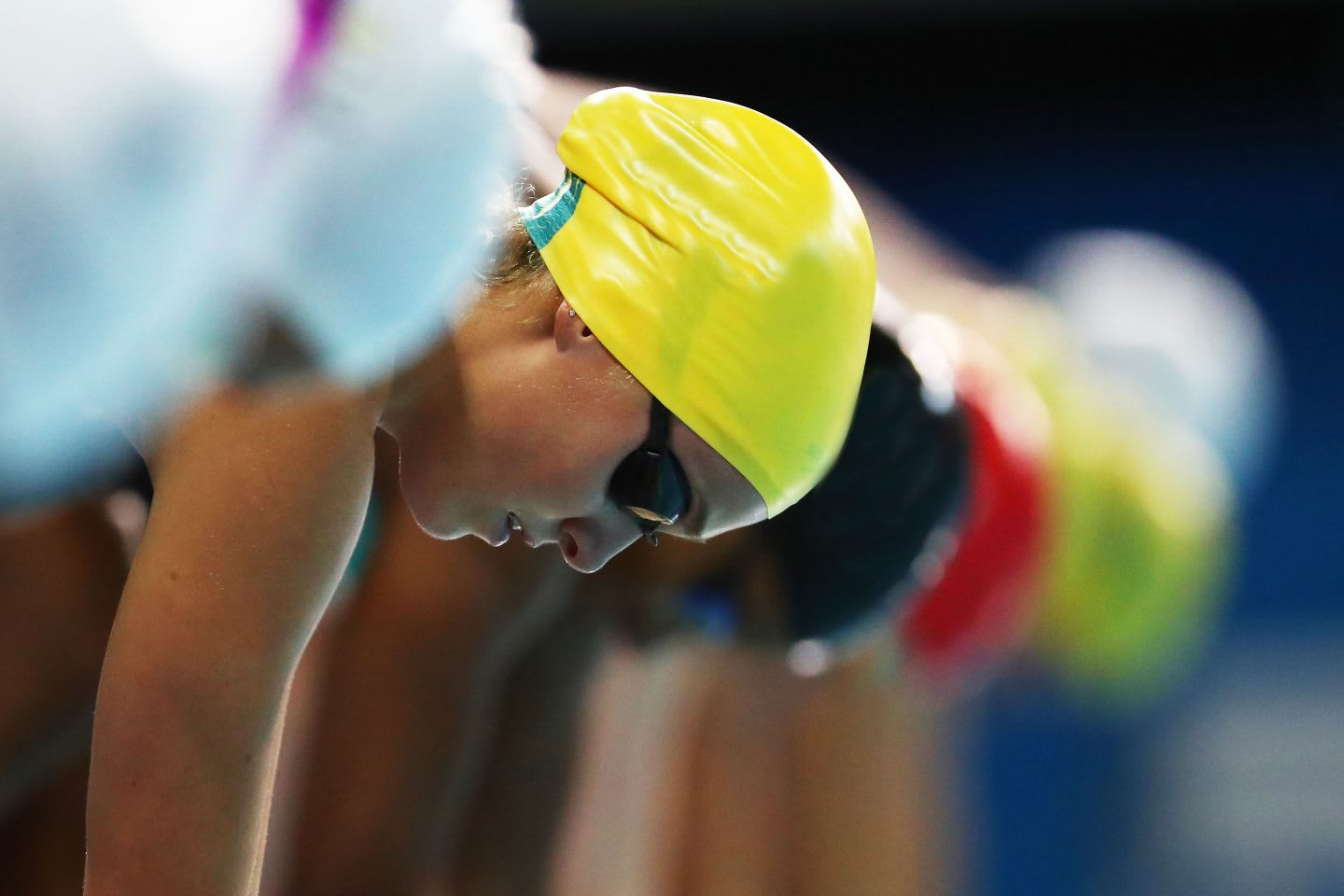 A line of swimmers take mark on the pool's edge in anticipation to dive into the pool. swimming, swimmer, competition, anticipation, focus
