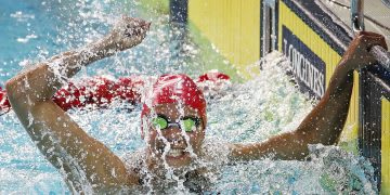 A female swimmer punches the air in victory of a swimming competition. victory, success, winning, swimming