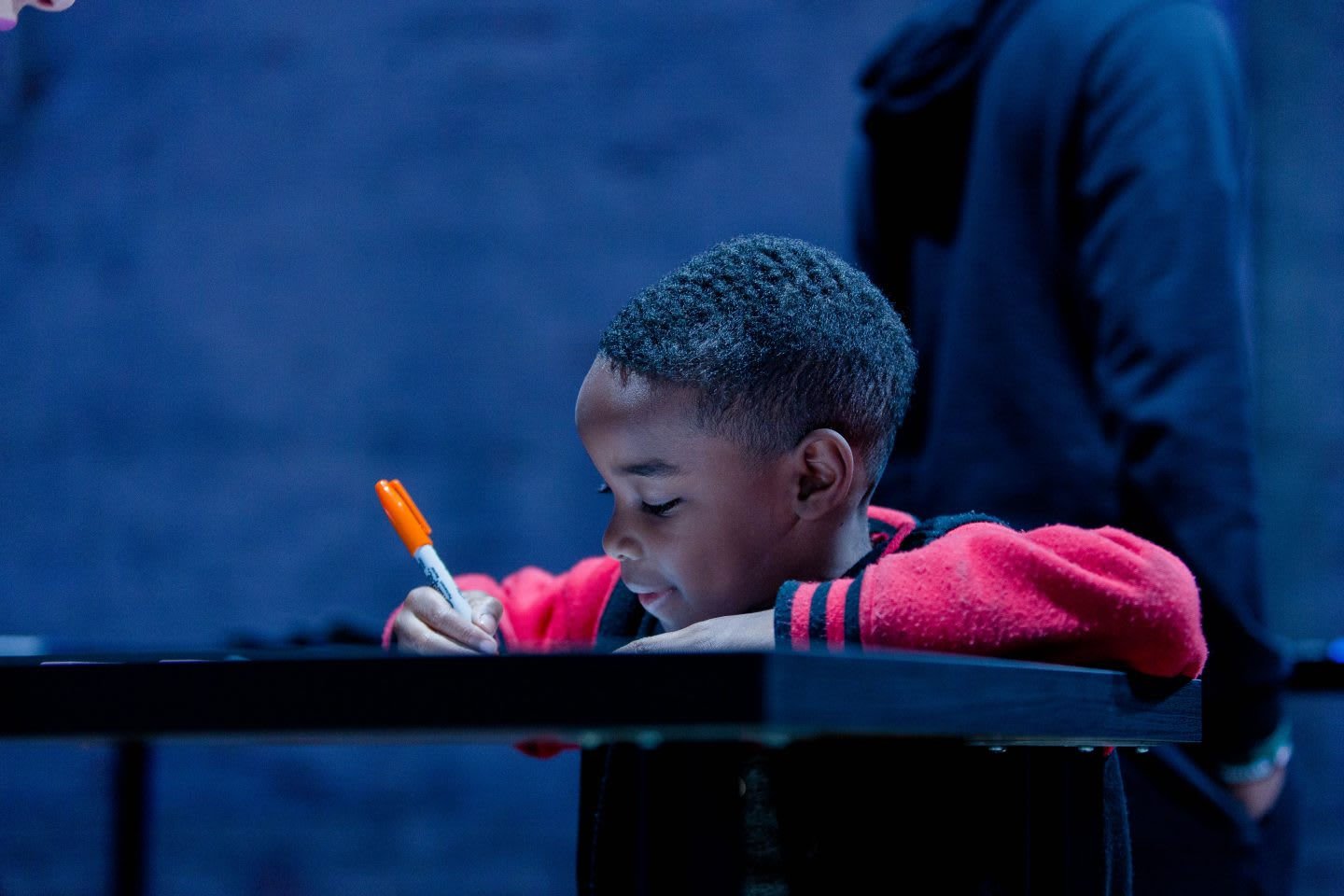 A little boy leans on a table as he draws on a piece of paper with a pen. creative, imagination, creativity, drawing