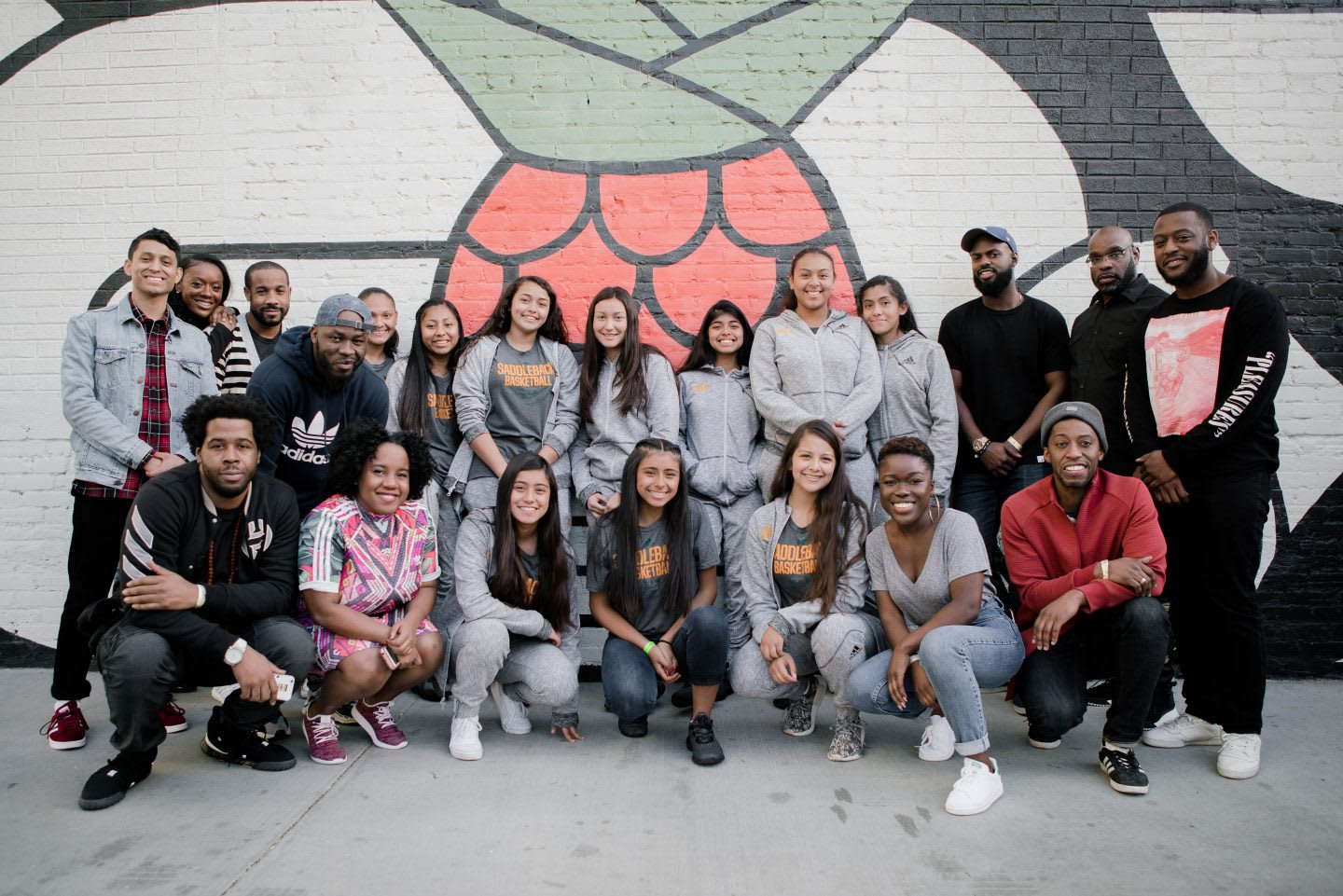 A group of youth and mentors pose for a group photo in front of a wall with a mural on it. team, teamwork, celebration, pride