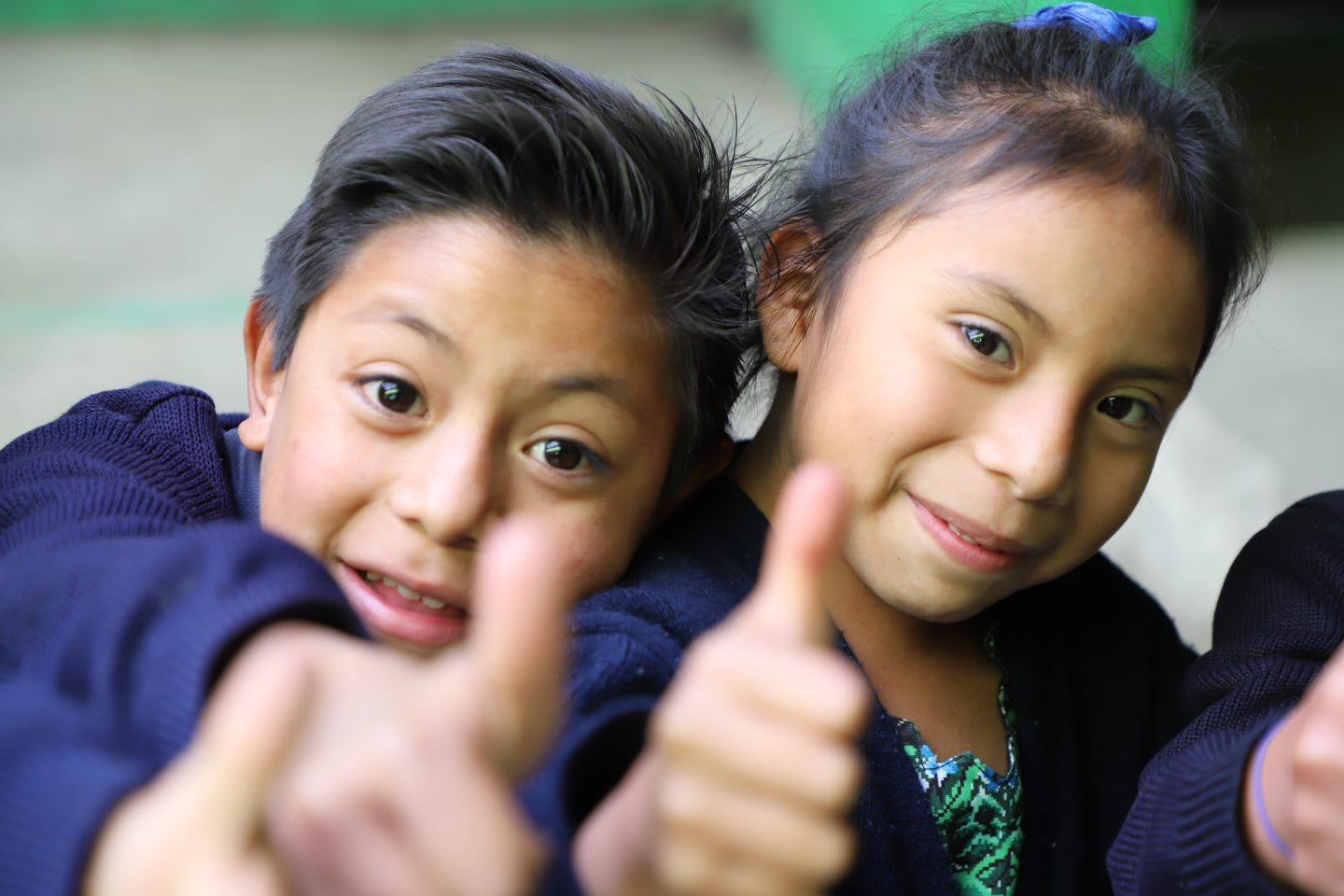 Two children hold their thumbs up smiling. happy, children, accomplishment, proud