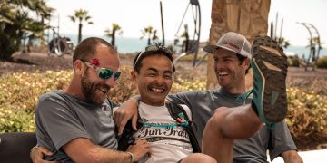 Three men sit down in laughter. men, friendship, joking, laughing