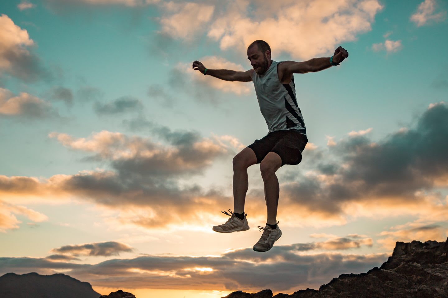 A man jumps for joy wearing running clothes in a sunset. running, sunset, joy, motivation, happy, concentration