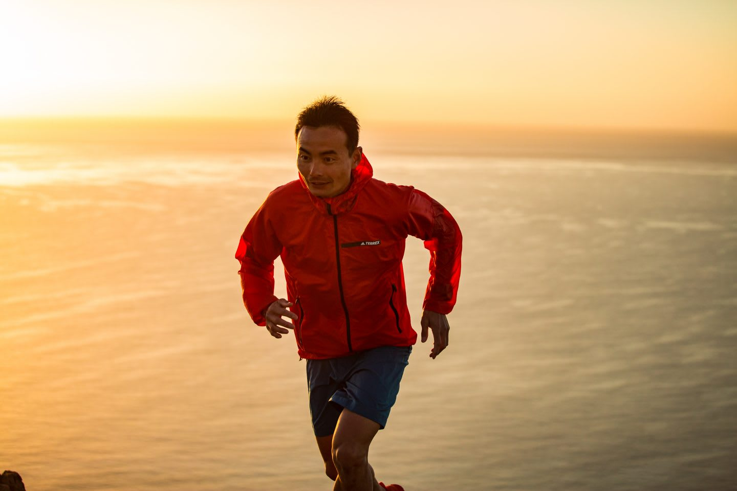 A runner looks focused on the trail ahead while running during the sunset. focus, running, runner, sunset, ocean