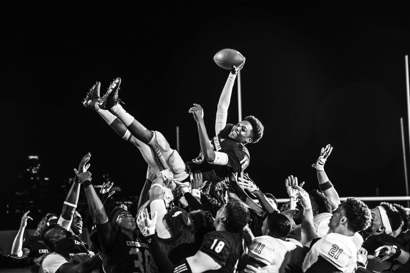 A team of american footballers hold up a team member in celebration of a win. american football, team, teammates, win, celebration