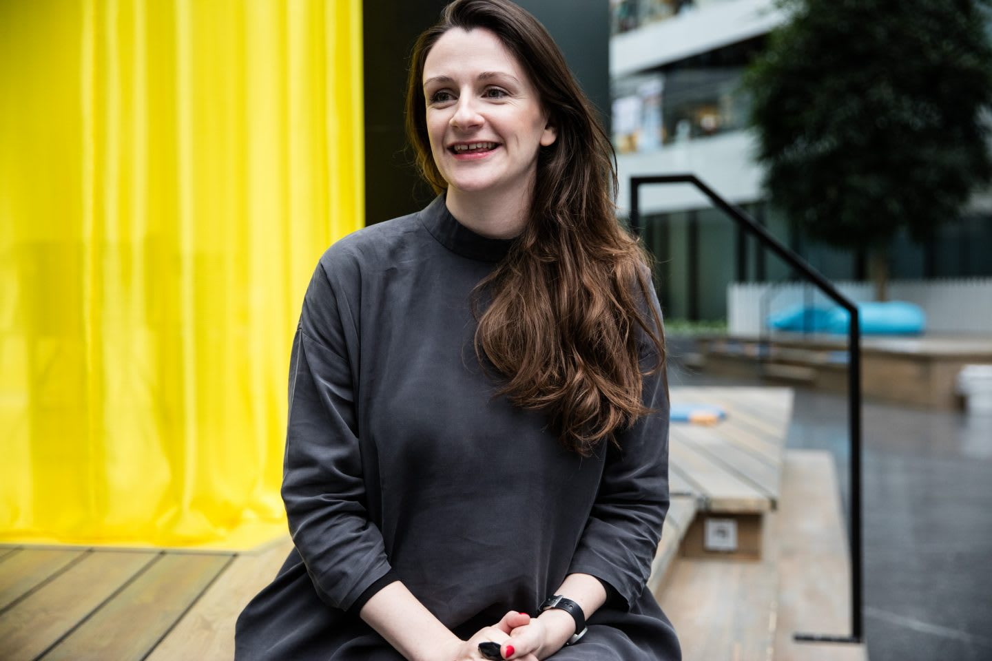 Woman sitting on a bench laughing at the adidas HQ. Lauren Currie, entrepreneur, public speaking, diversity, confidence, interview, GamePlan A