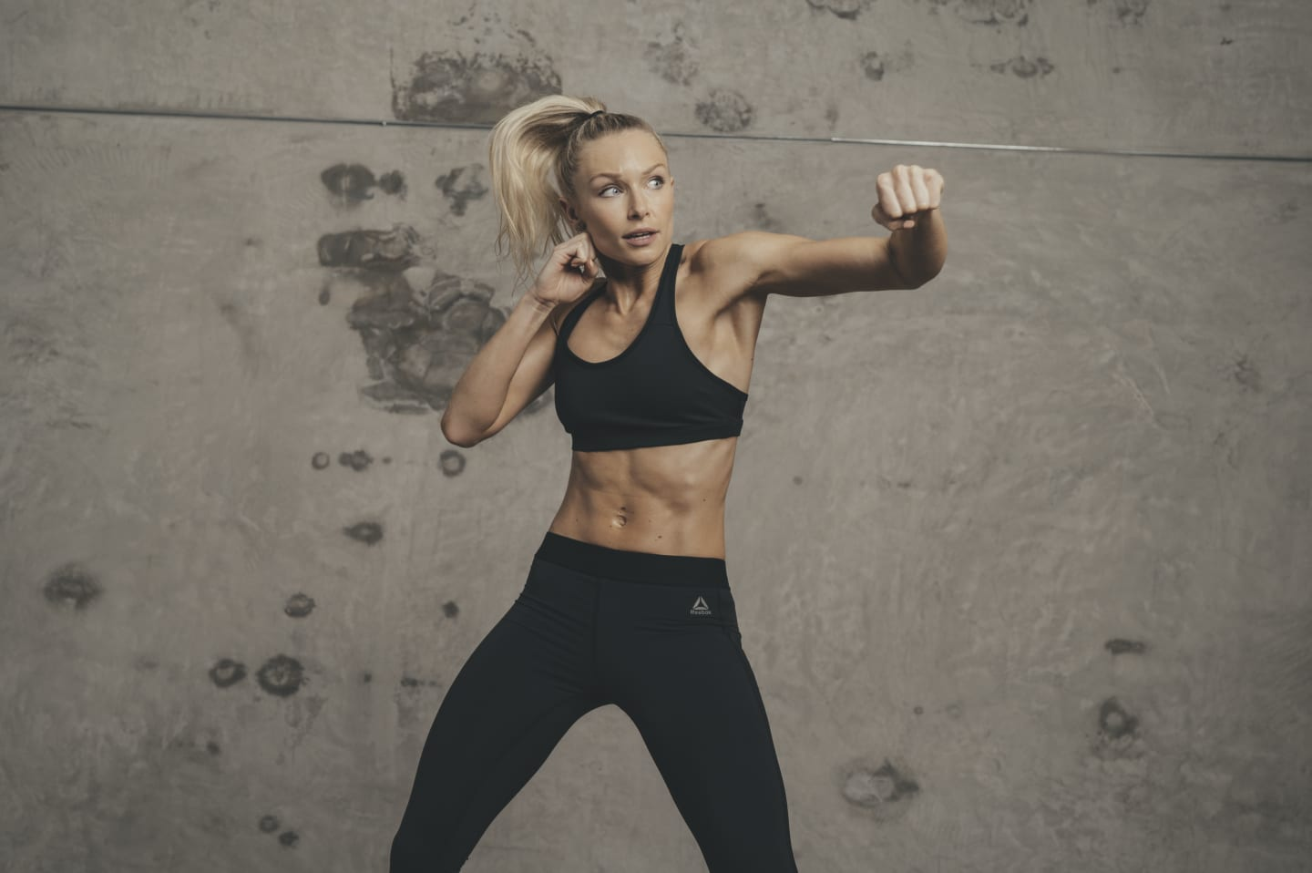 Woman doing shadow boxing in front of a grey wall.Woman-Fitness Boxing-class, GamePlan A, adidas