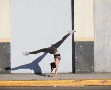 Woman doing a yoga handstand pose on the street. Sami Miro, yoga, Reebok
