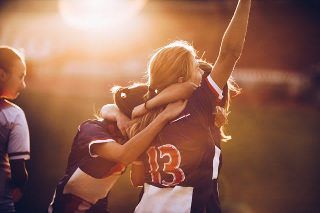 Team of happy female soccer players celebrating their achievement on a playing field at sunset. adidas, GamePlan A, self-reflection, impact