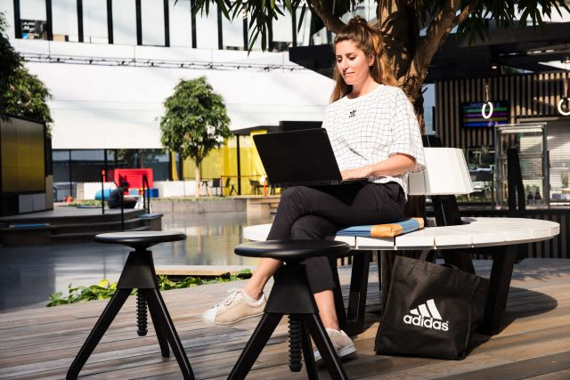 Woman sitting on a bench with a laptop on her knees at the adidas HQ. adidas employee-adidas HQ-flexible working