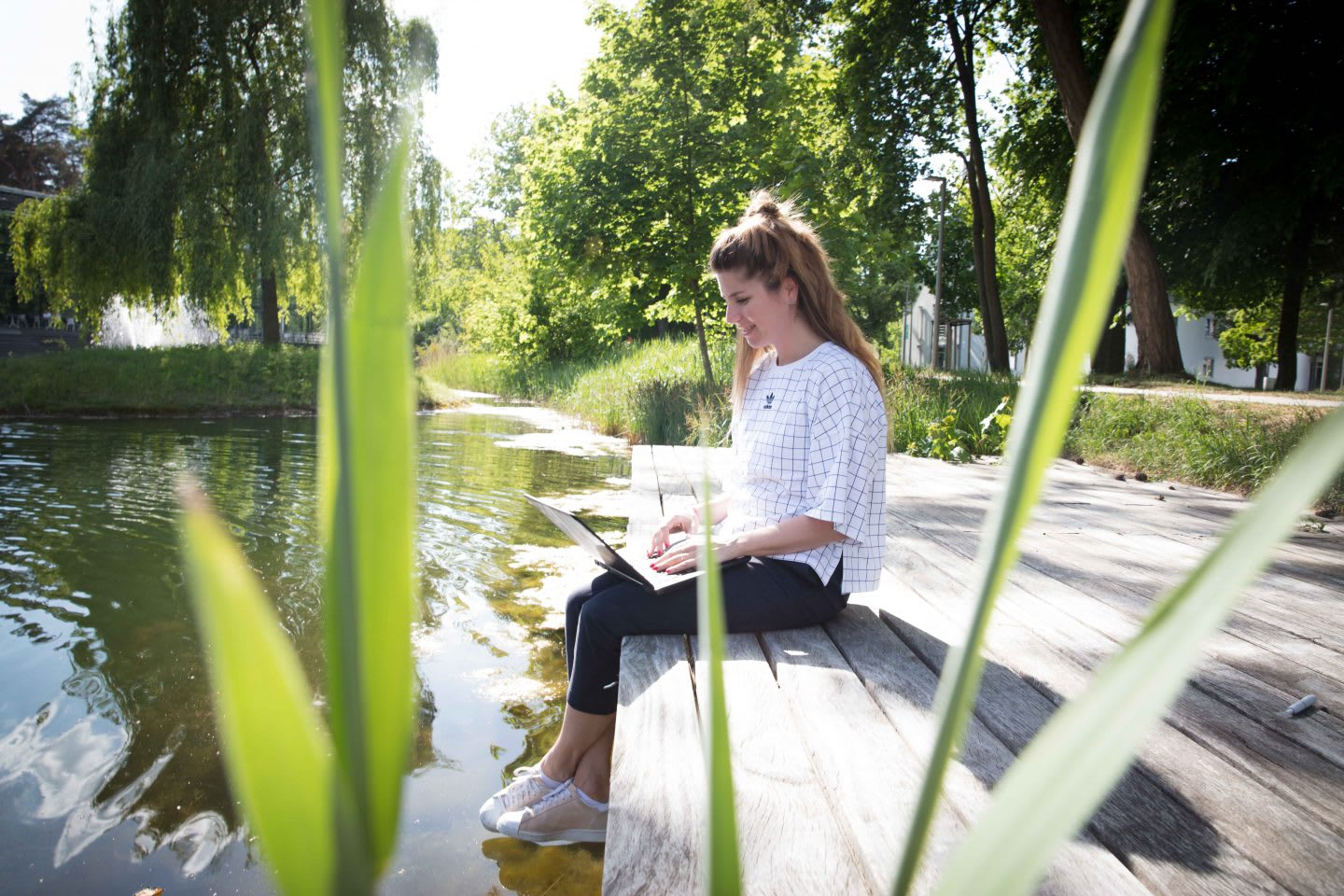 Woman working outside sitting on a land near a lake. adidas, GamePlan A, job, work life, lifestyle