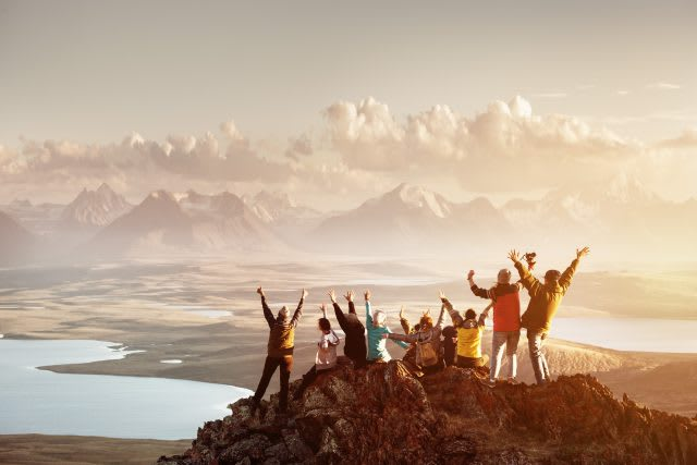 Big group of people having fun in success pose with raised arms on mountain top against sunset lakes and mountains. Travel, adventure or expedition concept, adidas, GamePlan A, team building, leadership, diversity, Latin America