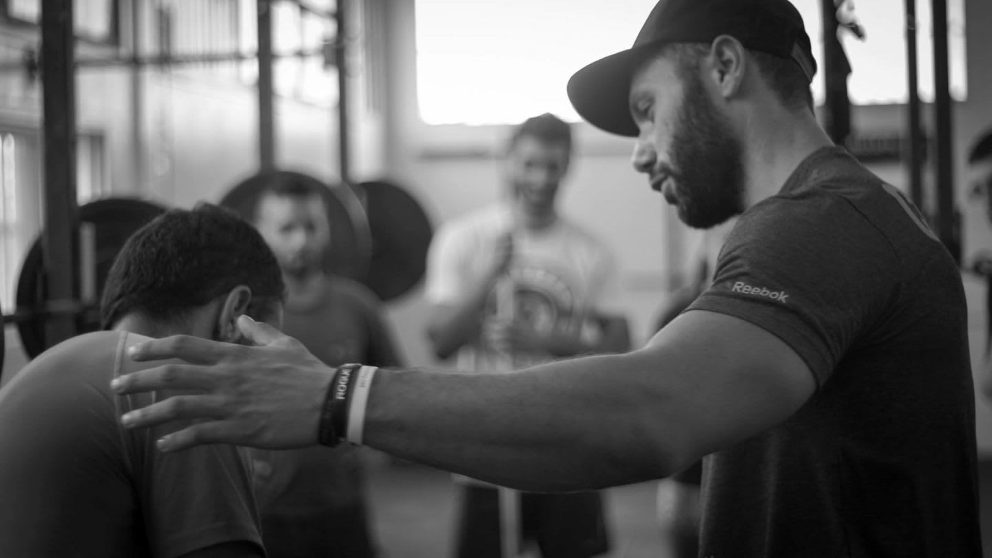 Black and white picture of a fitness coach helping an athlete with the execution of a fitness exercise. injury, adidas, GamePlan A, setback, coach, coaching, motivation, career